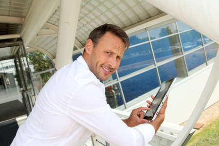 Businessman using electronic tablet outside the airport photo