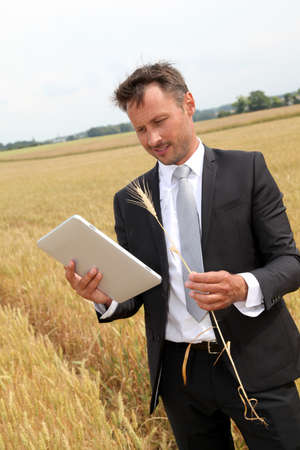 Businessman with electronic tablet standing in wheat field photo