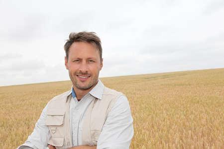 農家: 麦畑のなかに立っているハンサムな男の肖像