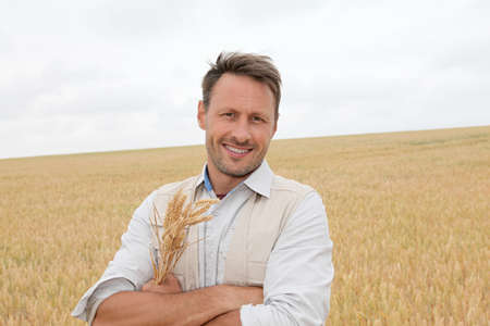 Portrait of handsome man standing in wheat field photo