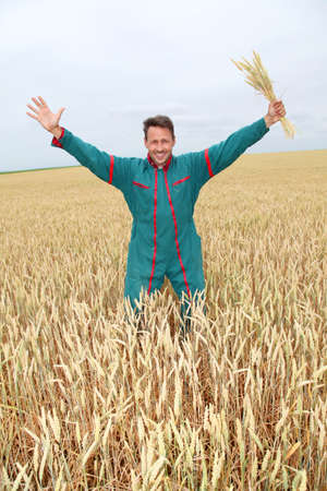 Farmer standing in wheat field with arms up photo