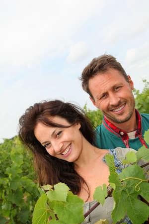 Happy couple of winegrowers in vineyard photo