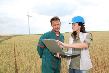 agronomist: Farmer and engineer in wheat field with wind turbines in background