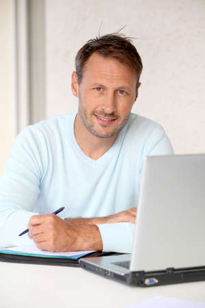 Man working at home on laptop computer photo