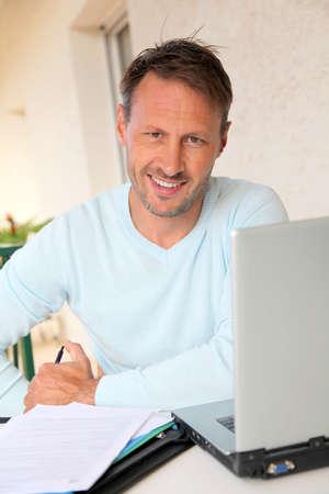 hombre escribiendo: Hombre que trabaja en su casa en la computadora port?til Foto de archivo