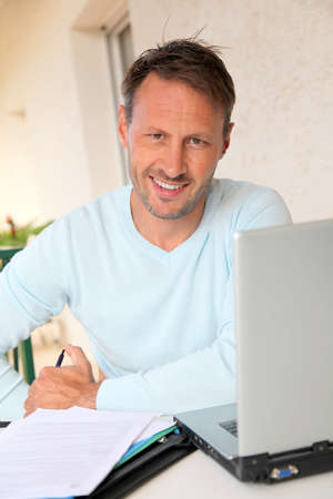 40 years old man: Man working at home on laptop computer
