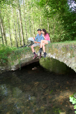 Couple sitting on a bridge in forest photo