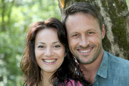 Portrait of smiling couple in forest photo