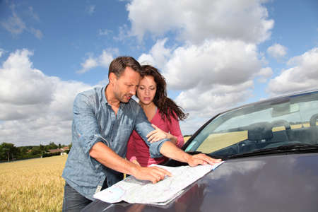 orientation: Couple looking at road map on car hood