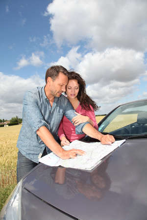 Couple looking at road map on car hood Stock Photo - 9901626