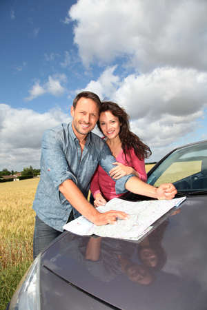 Couple looking at road map on car hood Stock Photo - 9901664