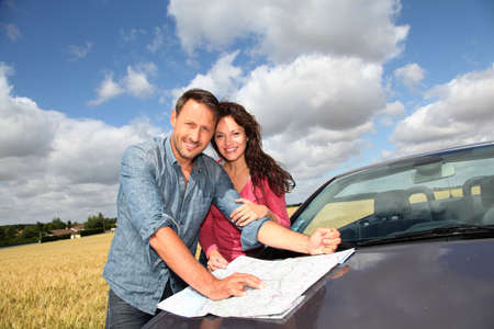 Couple looking at road map on car hood Stock Photo - 9908734