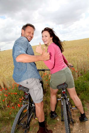 Smiling couple riding bicycle in country field photo