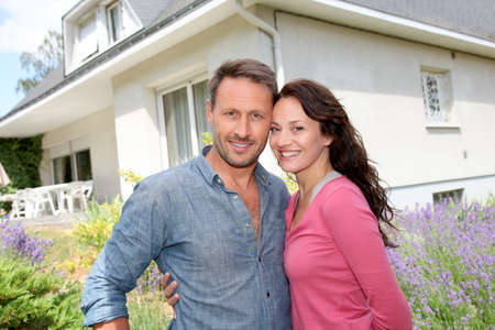 Happy couple standing in front of new home Stock Photo - 9911130