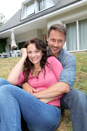 Portrait of happy couple sitting in front of their new house photo