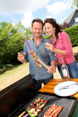 broil: Happy couple cooking meat on barbecue grill Stock Photo