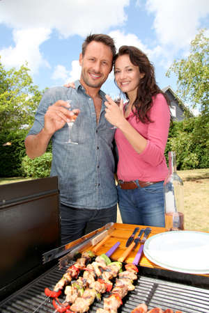 kebob: Happy couple cooking meat on barbecue grill Stock Photo