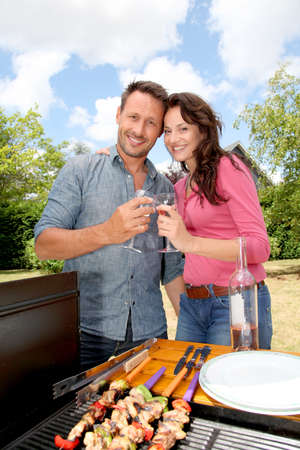 그릴: Happy couple cooking meat on barbecue grill 스톡 사진