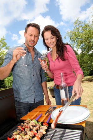 garden party: Happy couple cooking meat on barbecue grill Stock Photo