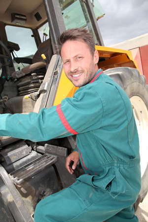 Farmer climbing in tractor photo