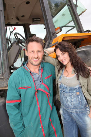 old tractor: Farming couple standing by tractor Stock Photo