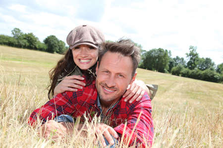 Happy couple laying down meadow photo