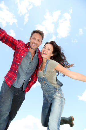 arms in air: Couple jumping in the air Stock Photo