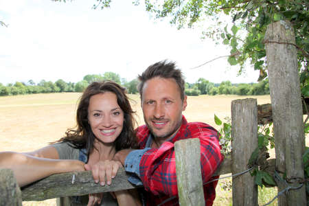 breeder: Couple leaning on fence in country field Stock Photo