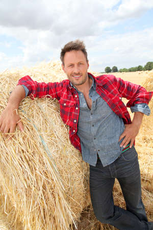 Handsome farmer standing by hay bale photo