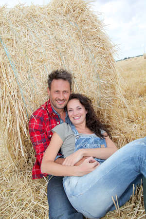 Couple relaxing in hay bales photo