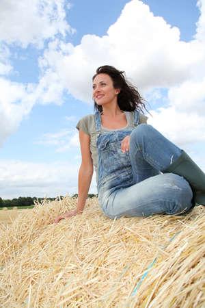overalls: Woman having fun sitting on hay bale