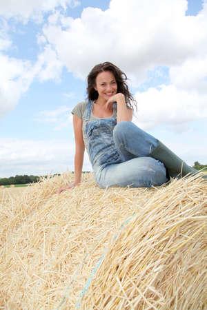 Woman having fun sitting on hay bale photo