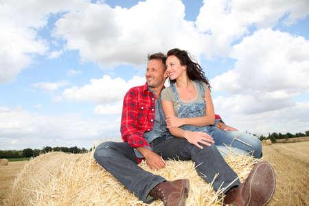 Happy couple sitting on bale in farmland photo