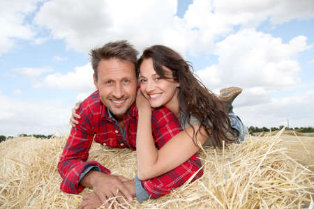 Happy couple sitting on bale in farmland photo