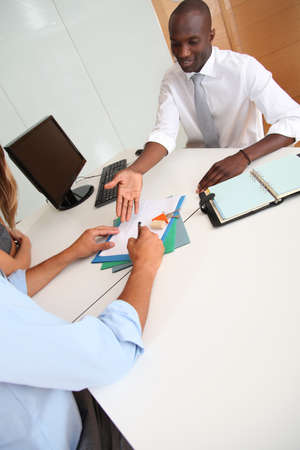 Real-estate agent with couple signing contract photo