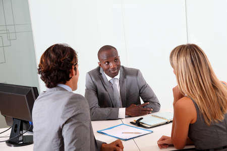 businessman signing documents: Couple meeting businessman in office