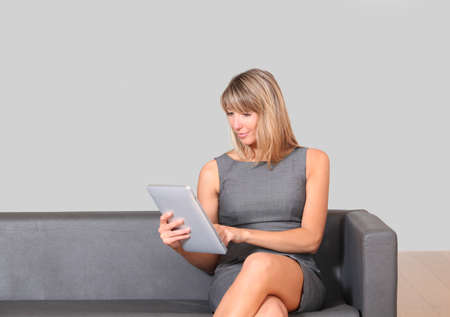 Businesswoman using electronic tablet in waiting room photo