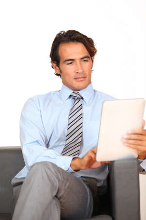 Businessman using electronic tablet in waiting room photo