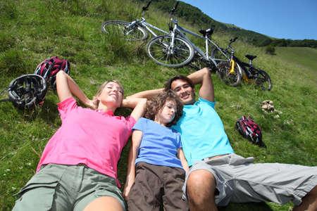 ni�os en bicicleta: Familia descansa en la naturaleza durante el paseo en bicicleta