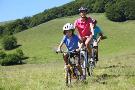 Family on a mountain bike ride in summer photo