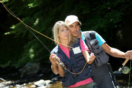 fisherwoman: Couple flyfishing in river during summer vacation