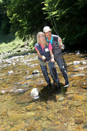 waders: Couple flyfishing in river during summer vacation