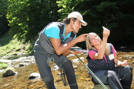 Couple looking at fishing flies in river Stock Photo - 9910427