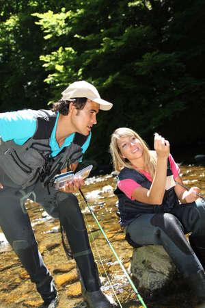botas altas: Couple looking at fishing flies in river