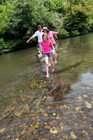 두서없는: Family crossing river barefoot