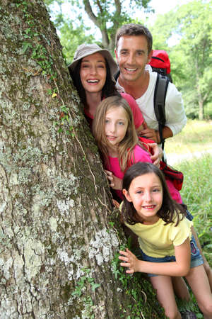 happy family nature: Portrait of happy family standing by a tree
