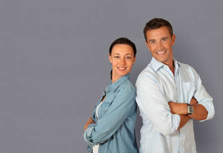 Couple standing on grey background with arms crossed photo