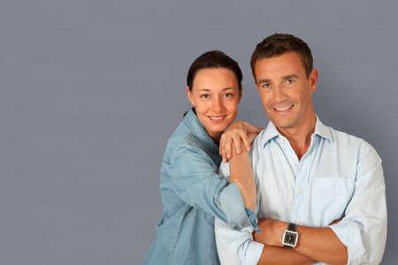 Happy couple standing on grey background photo