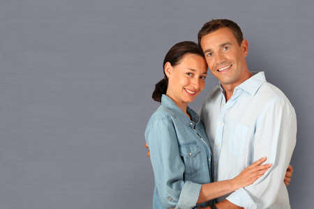 Portrait of couple standing on grey background photo