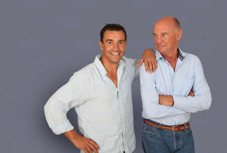 Portrait of father and son on grey background photo